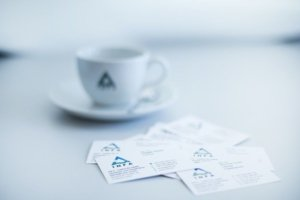 Kaffeetasse mit INFA Logo und Visitenkarten