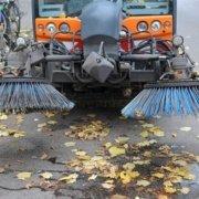 Straßenkehrmaschine die Laub kehrt