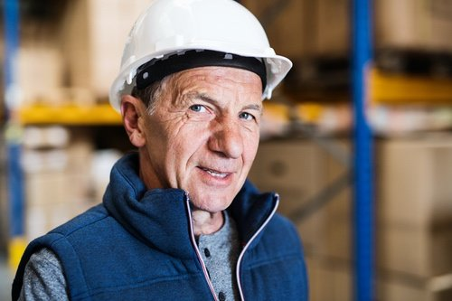 Älterer Mann mit Arbeitshelm
